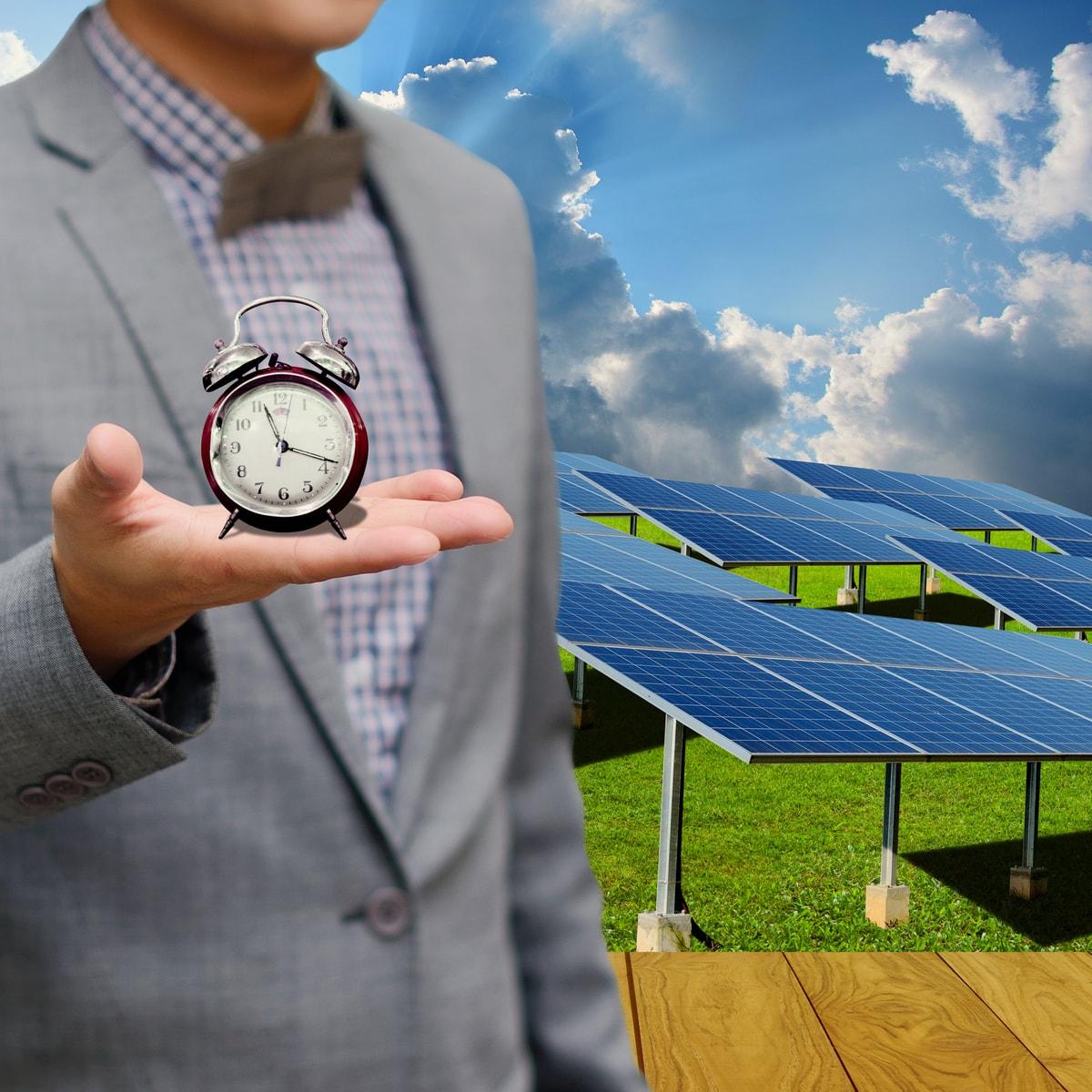 un uomo tiene un orologio in mano con lo sfondo un impianto fotovoltaico. Illustra che per avere un impianto attivo bisogna attendere i tempi di connessione e autorizzazione.